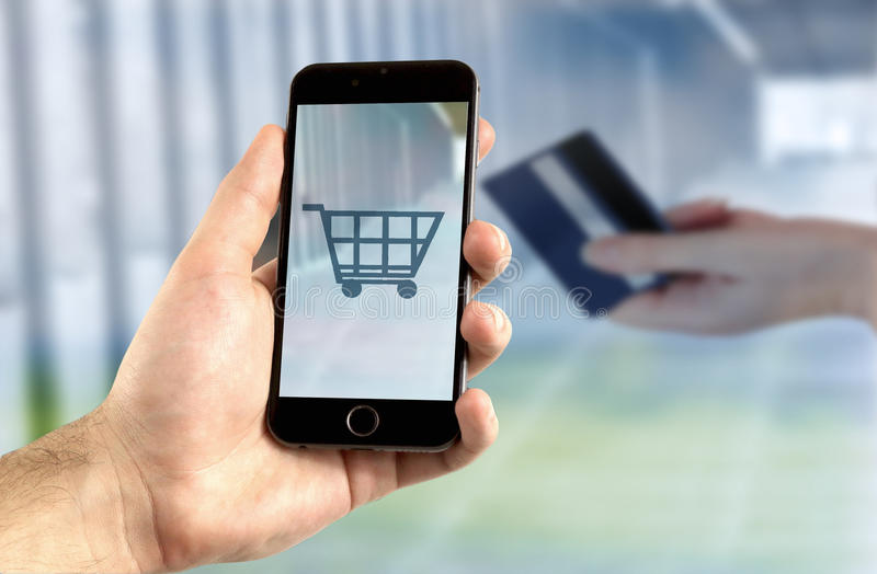 Mobile banking concept. Hand holding mobile phone for internet shopping with shopping cart symbol royalty free stock photos