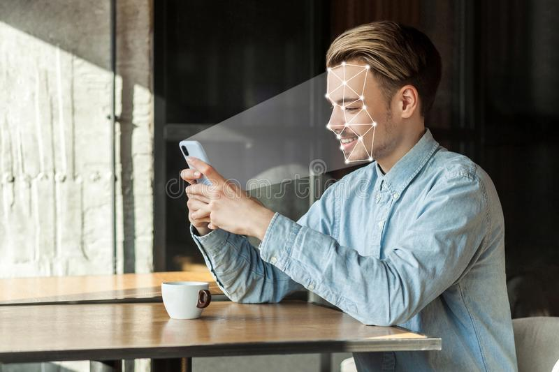 Mobile biometric identification and verification face detection concept. face ID scaning or unlocking technology. Young happy man sitting and scanning face royalty free stock photography