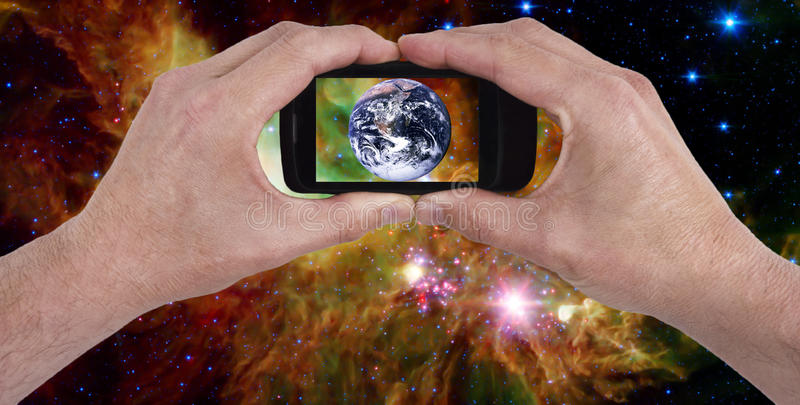 Mobile Cell Smart Phone, Earth, Space, Universe. Concept for communications and modern technology. Hands are holding a smart mobile cell phone with an image of stock image