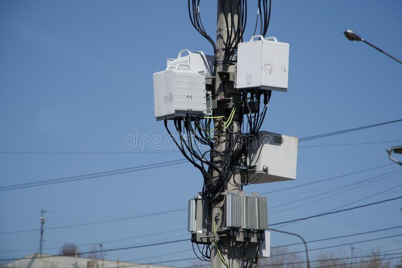 Mobile cellular station and wireless Internet on the pole among the wires in an urban setting. Urban economy royalty free stock image