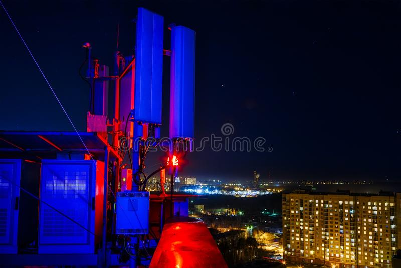 Mobile communications mast antenna atop a tall building, against night city. Mobile communications mast antenna atop tall building, against night city royalty free stock photography