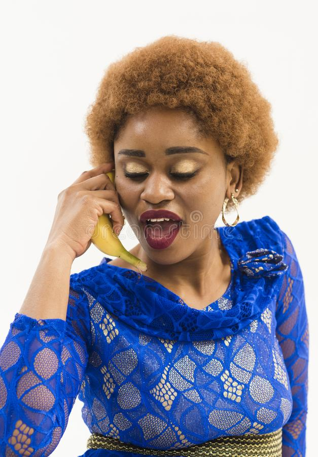 Mobile connection concept. Lady with banana near ear. Lady on busy face and afro hairstyle talking. Woman with african. Appearance in blue dress speak on banana royalty free stock images