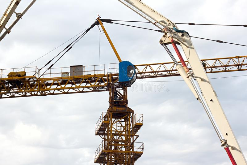 Mobile construction cranes with yellow telescopic arms and big tower cranes in white clouds and deep blue sky on background, heavy royalty free stock photos