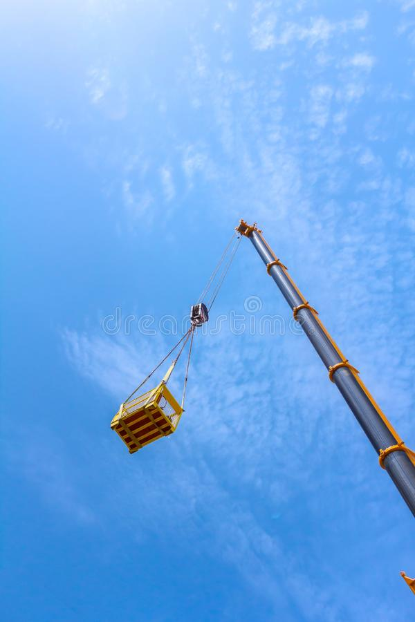 Mobile crane is lifting cargo in work platform, basket stock image