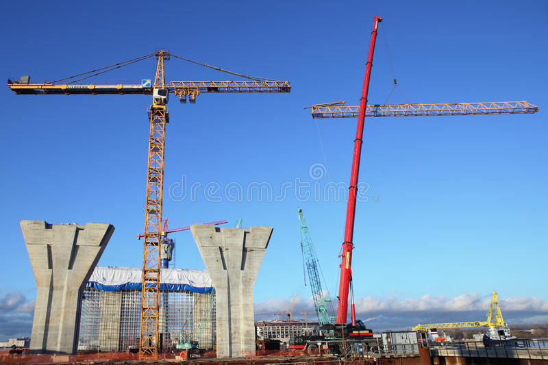 Mobile crane lifts up a section of the tower crane. St. Petersburg, Russia - October 30, 2014: Construction plant, Erection of the towers crane, connecting royalty free stock photo