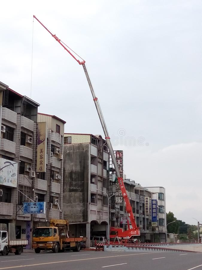 The mobile crane is working, in Taiwan. A mobile crane is a cable-controlled crane mounted on crawlers or rubber-tired carriers or a hydraulic-powered crane stock photography
