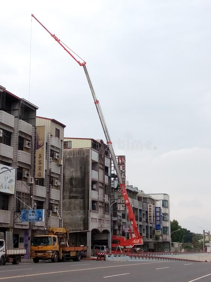 The mobile crane is working, in Taiwan. A mobile crane is a cable-controlled crane mounted on crawlers or rubber-tired carriers or a hydraulic-powered crane stock photo