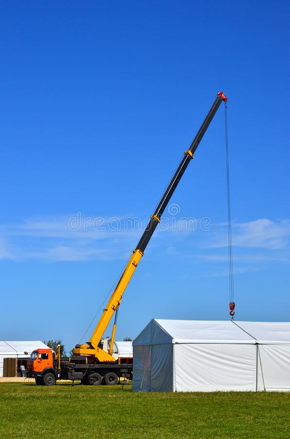 Mobile crane with yellow arrow lift a heavy load against the blue sky, construction of an industrial facility, houses, buildings.  stock image