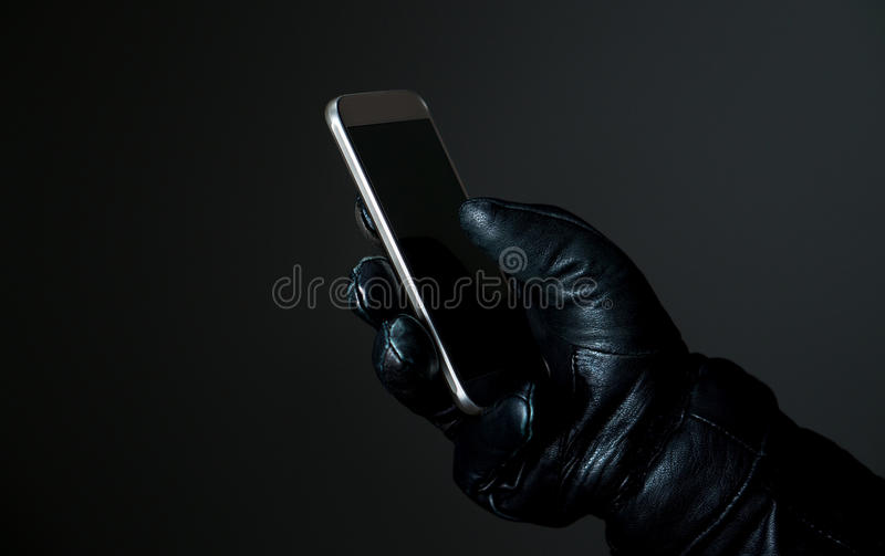 Mobile and cyber security. Criminal holding smartphone with black leather gloves in darkness. Hacker touching smart phone screen. Mobile and cyber security stock photography