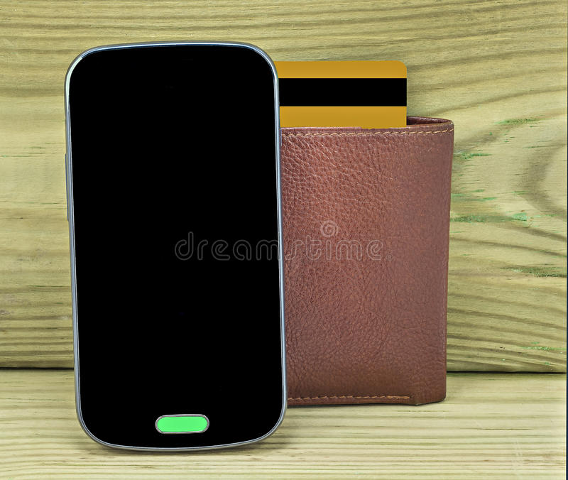 Mobile devise with wallet and credit card. On wood background royalty free stock photos
