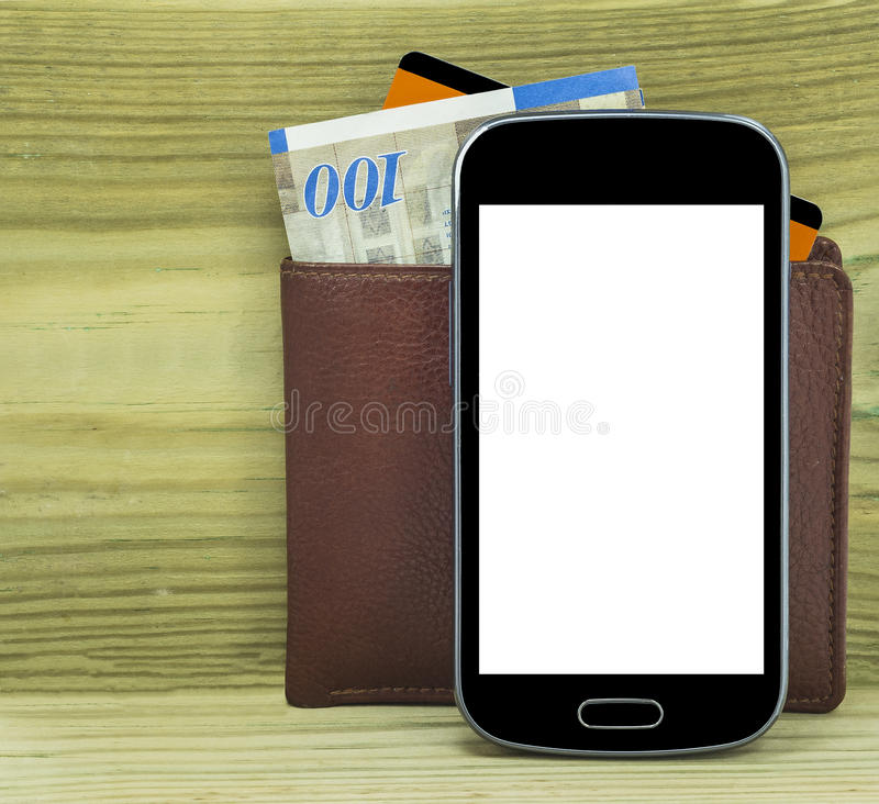 Mobile devise with wallet, money and credit card i. Solated on wood background royalty free stock photo