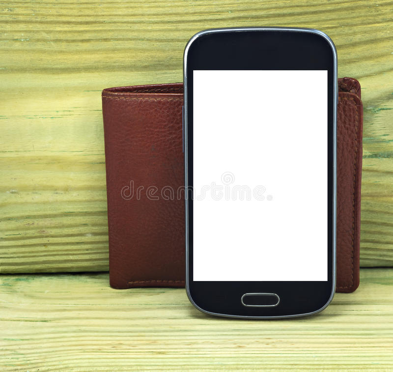 Mobile devise with wallet on wood. Background stock images