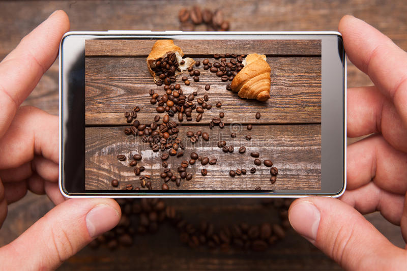 Mobile food photography. Phone in hands stock photography