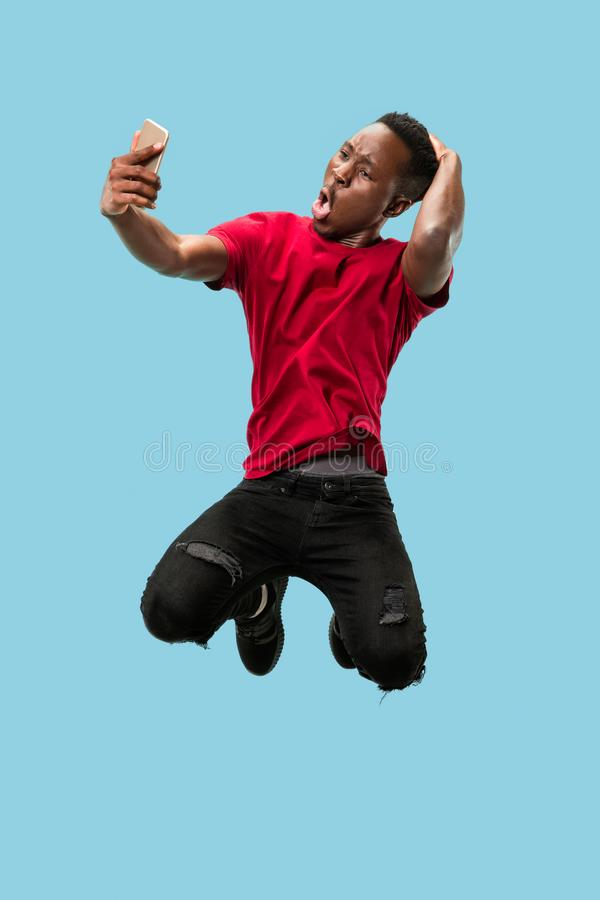 Always on mobile. Full length of handsome young man taking phone while jumping. Always on mobile. Full length of handsome african young man taking phone while stock image