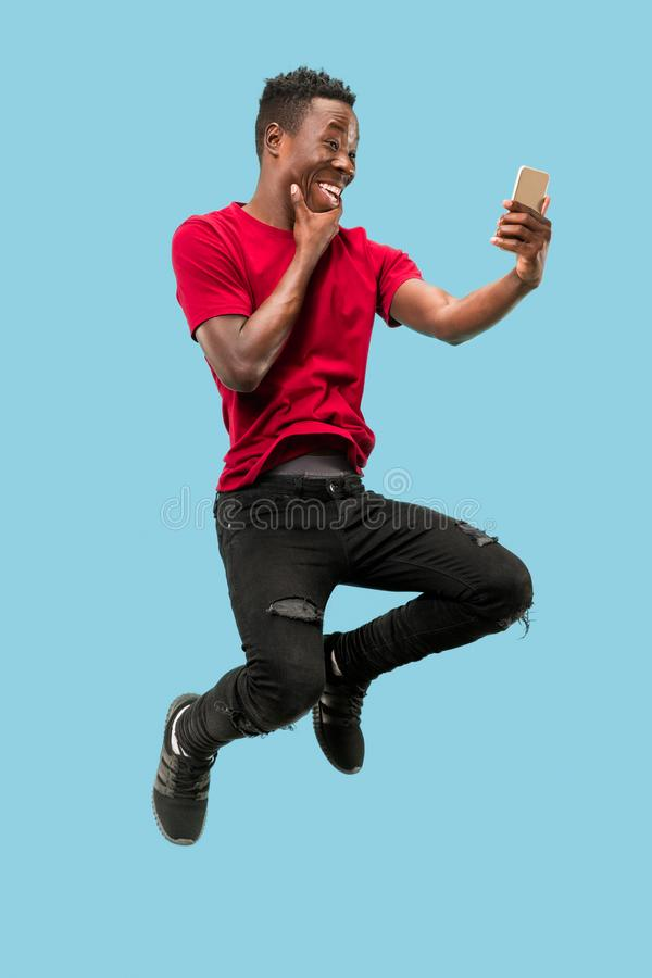 Always on mobile. Full length of handsome young man taking phone while jumping. Always on mobile. Full length of handsome african young man taking phone while royalty free stock photos