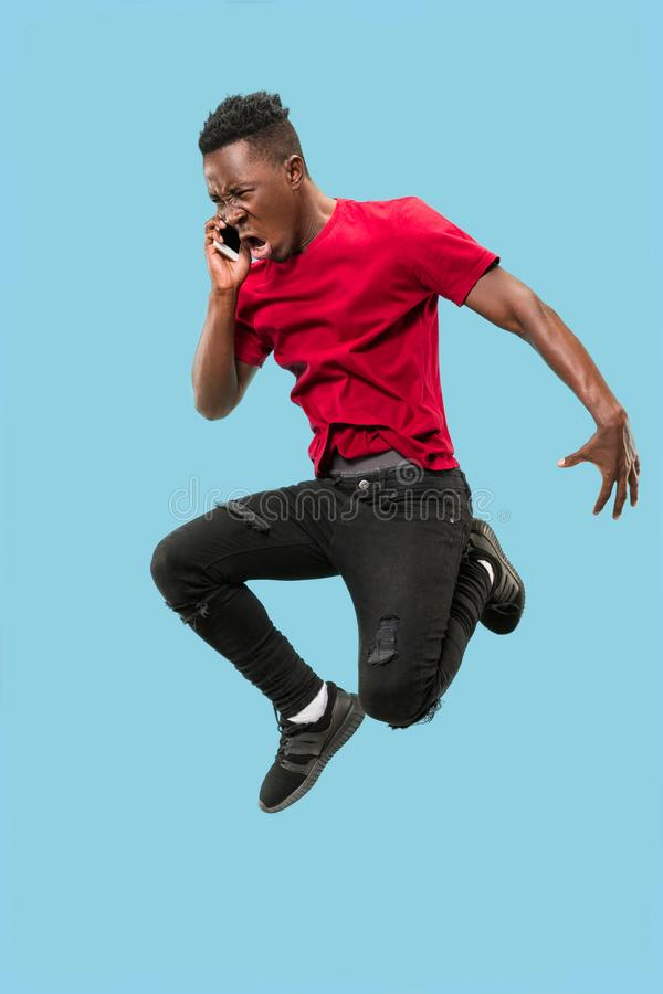 Always on mobile. Full length of handsome young man taking phone while jumping. Always on mobile. Full length of handsome african young man taking phone while royalty free stock photo