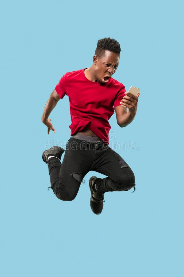 Always on mobile. Full length of handsome young man taking phone while jumping. Always on mobile. Full length of handsome african young man taking phone while stock images