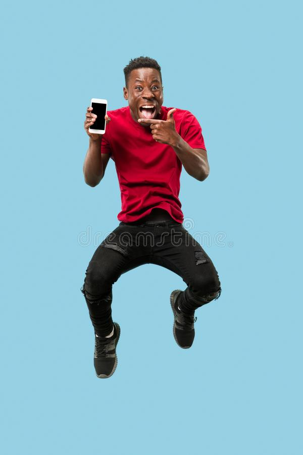 Always on mobile. Full length of handsome young man taking phone while jumping. Always on mobile. Full length of handsome african young man taking phone while stock photo