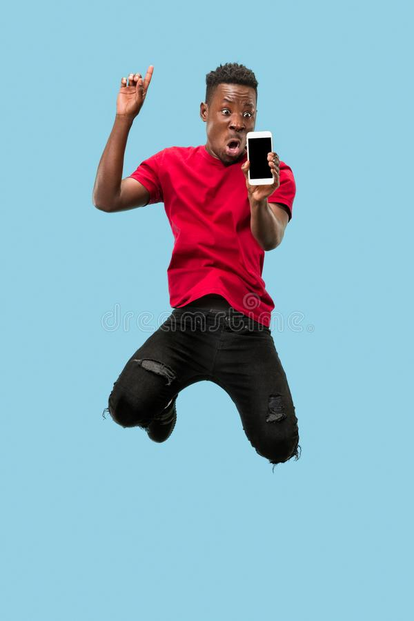 Always on mobile. Full length of handsome young man taking phone while jumping. Always on mobile. Full length of handsome african young man taking phone while stock photography