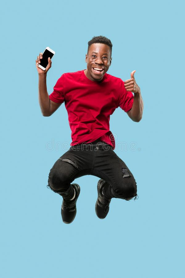 Always on mobile. Full length of handsome young man taking phone while jumping. Always on mobile. Full length of handsome african young man taking phone while royalty free stock photography