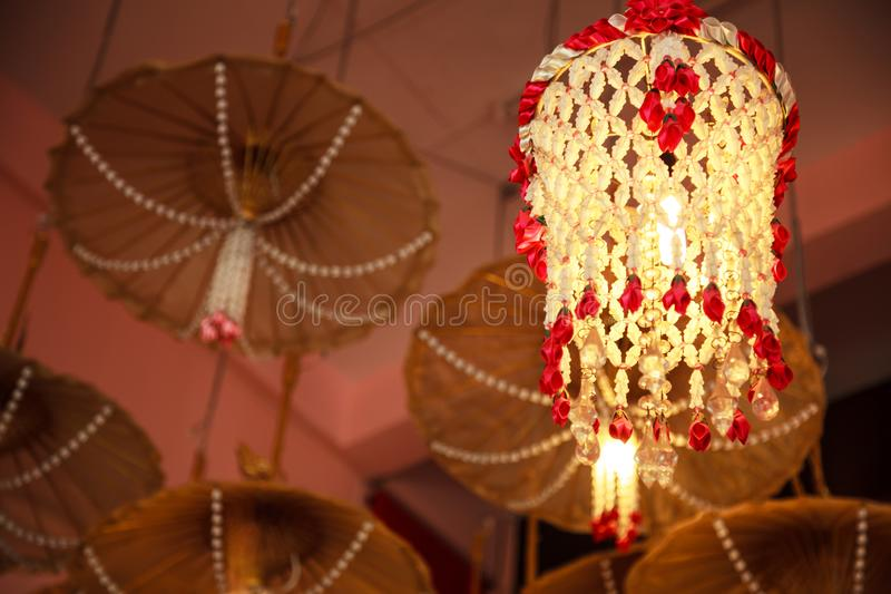 Mobile garland ceiling hanging lamp decorating furniture with wooden umbrellas background, house home interior architecture design. Traditional light room stock photography