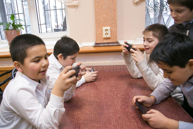 Mobile generation kids using their mobile devices for entertainment stock image