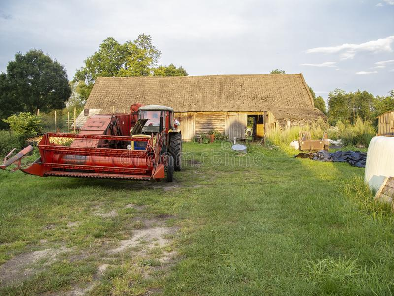 Mobile harvester connected to the tractor stock photo