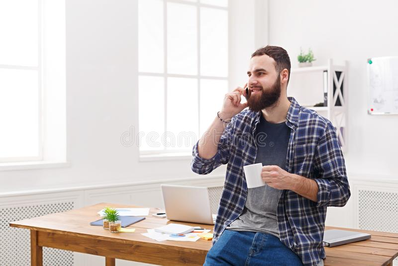 Mobile heureux et décontracté d'entretien d'homme d'affaires dans le bureau image stock