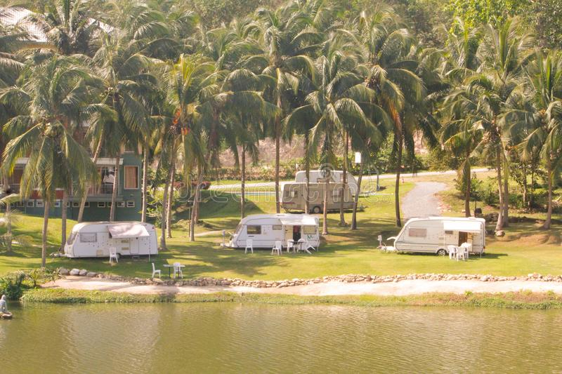 Mobile home cars parked in many coconut groves along the waterfront. Mobile home cars parked in many coconut groves along the waterfront stock photo