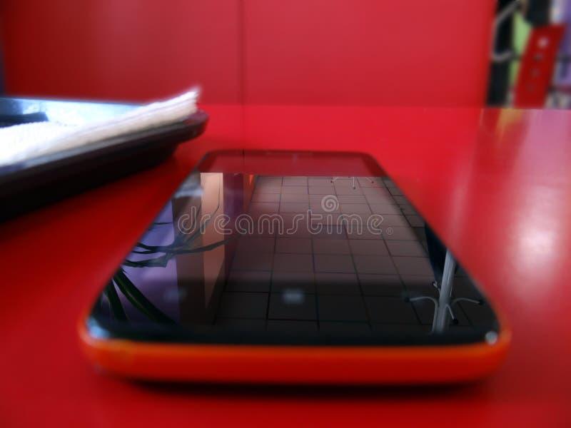 Mobile im roten Café lizenzfreies stockbild