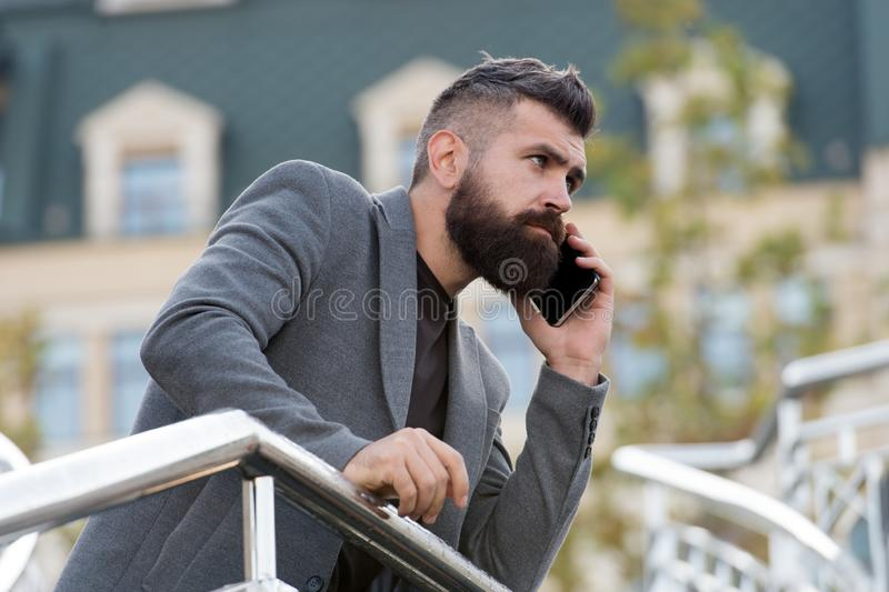 Mobile is lifestyle. Project manager use mobile device outdoor. Bearded man talk on mobile phone. Mobile business. Communication. Modern life. New technology royalty free stock image