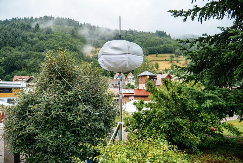 Mobile meteo station with houses of Ottenhofen im Schwarzwald,. Germany in the background and green forest covered with fog stock image