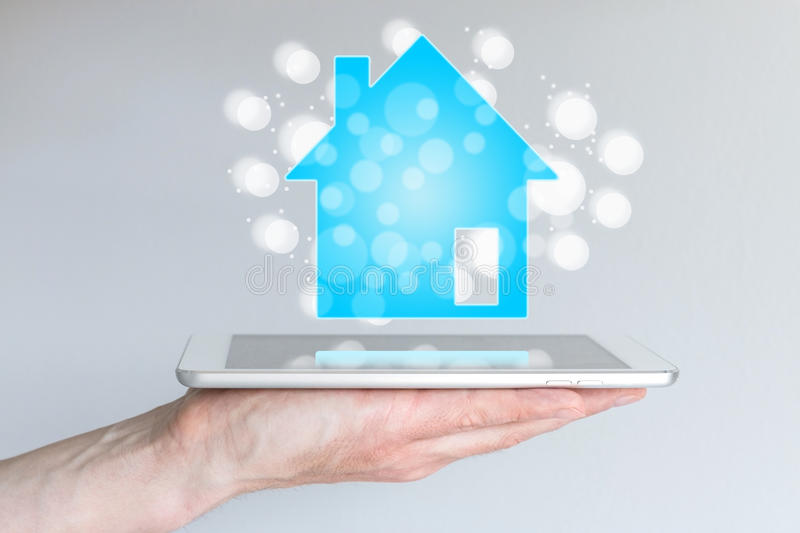 Mobile and online real estate and property sales with smart phone and tablet. Hand holding modern smart phone or tablet royalty free stock photo