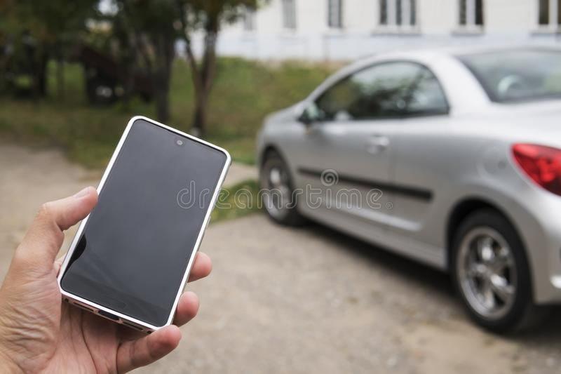 Mobile phone apps for car owners concept. Man using smart phone to check status, control his new car. Blank Empty mobile stock image