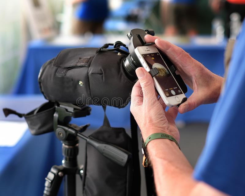 Mobile phone attached to viewing scope as visual aid device. royalty free stock photography