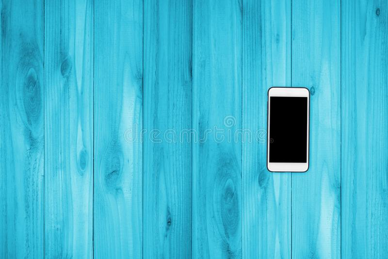 Mobile phone with black screen mock up on wood stock photo