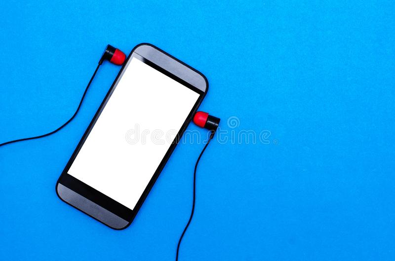Mobile phone and headphones. Mobile phone with blank screen and headphones isolated on a blue background, music, earphones, empty, template, mock, up, mockup royalty free stock photos