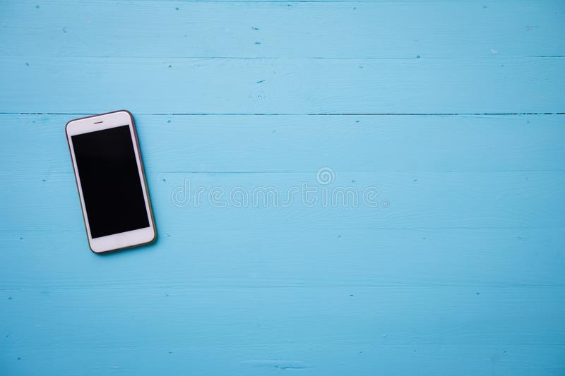 Mobile phone with blank screen mock up. On pink wood table background stock photography
