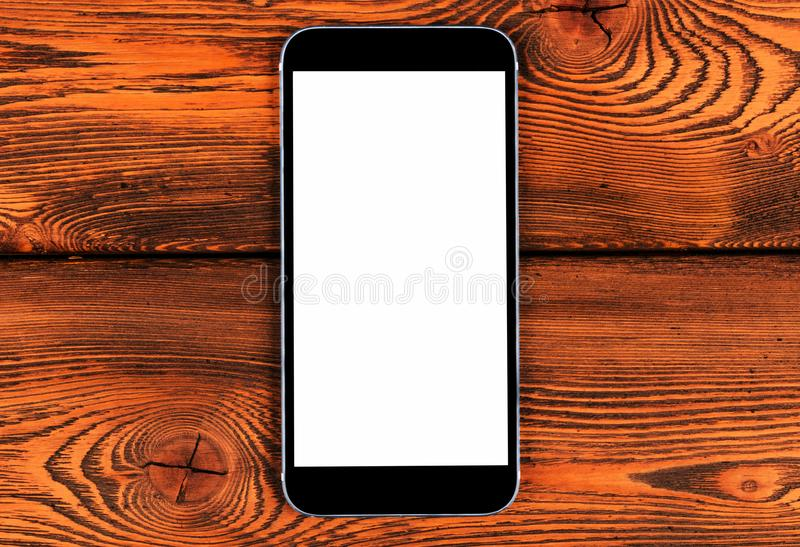 Mobile phone with blank screen mock up on yellow wood table background. Smartphone on wood table. Smartphone white screen royalty free stock photos