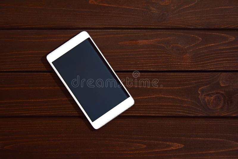 Mobile phone with blank screen on wooden table background. Smartphone on wood old plank vintage texture background. top view stock photo