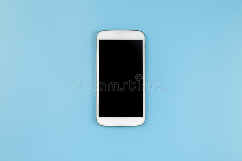 Mobile phone on blue background pastel style flatlay topview cop. Yspace clipping path at screen royalty free stock photography