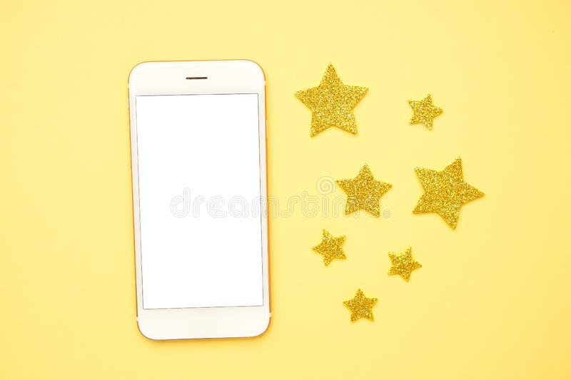 Mobile phone and brilliant glitter stars on a yellow background, technology and rating royalty free stock photos
