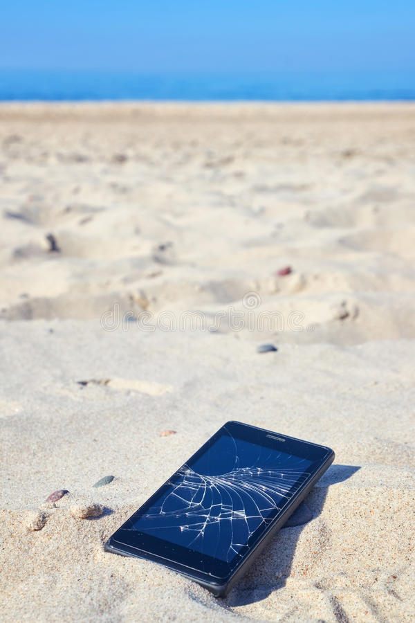 Mobile phone with broken screen in sand on a beach. Close up picture of a mobile phone with broken screen in sand on a beach, selective focus royalty free stock images
