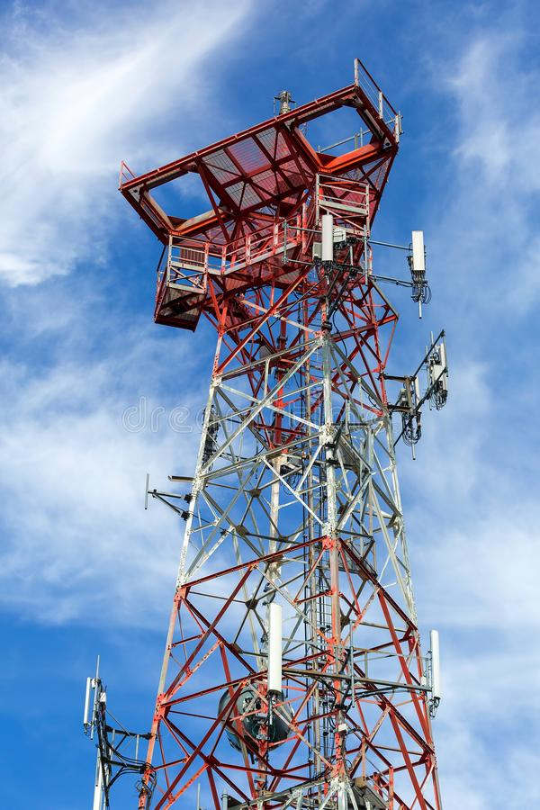 Mobile Phone Cellular Tower against blue sky and white clouds. Mobile phone communication internet signal cell tower against white clouds and blue sky royalty free stock photography