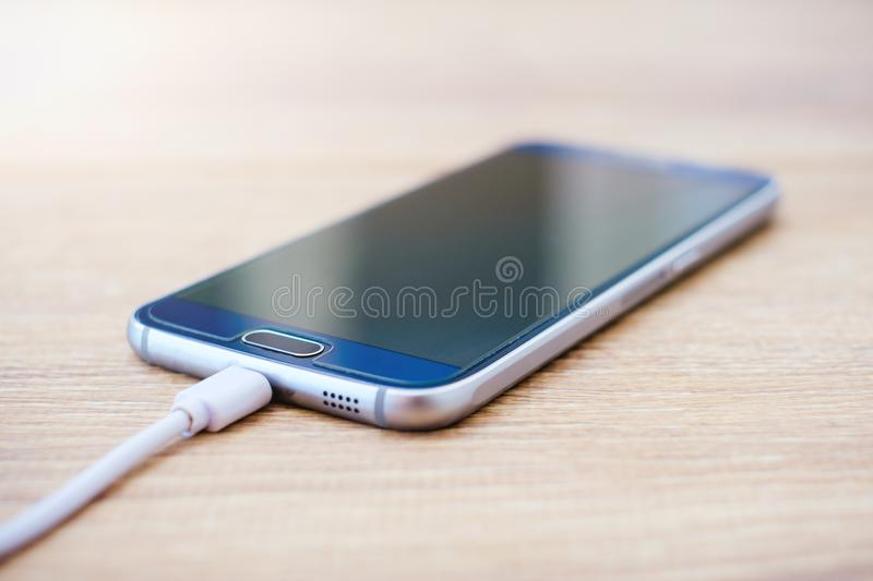 Mobile phone and battery charger cable on office desk stock photos