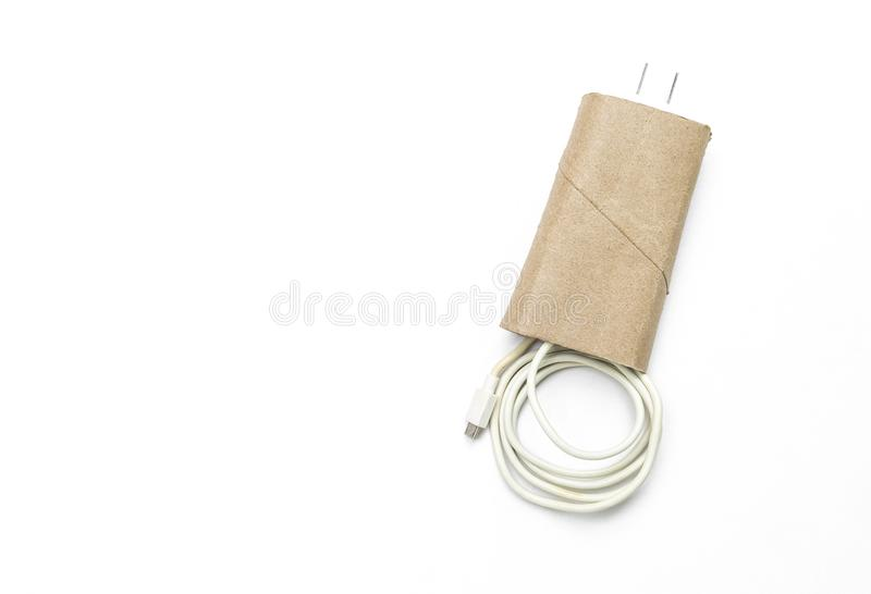 Mobile phone charger kept in toilet paper core, DIY cable storage royalty free stock photography