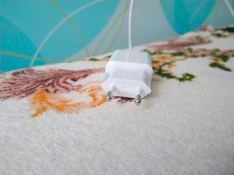 The mobile phone charger with wall outlet in bedroom royalty free stock photography