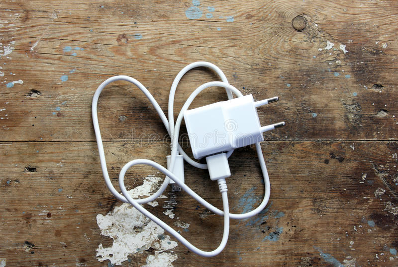 Mobile phone charger. White mobile phone charger on rustic wooden backround royalty free stock photography