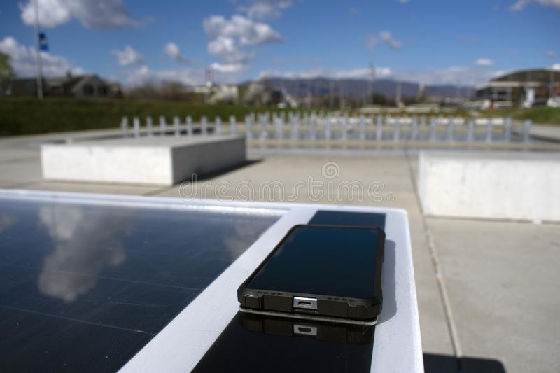 Mobile phone charging remotely on a solar bench royalty free stock image