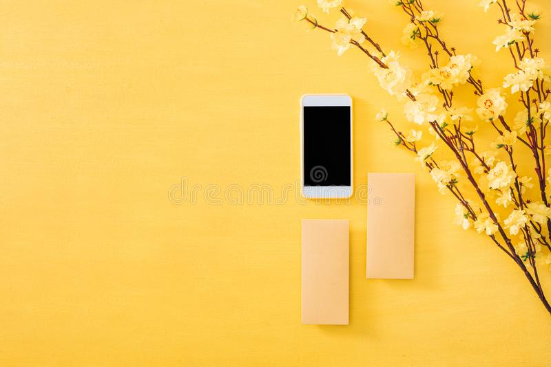 Mobile phone with Chinese New Year decoration on a yellow gold background stock image